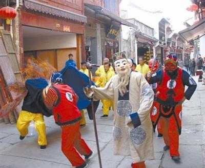 昨日下午,祁门县16位农民组成的傩舞队正在黄山屯溪老街巡演。今日起,他们将赴上海,为高校师生和市民表演。本报记者 吴永泉/摄