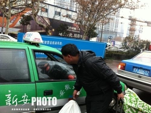 合肥明光路汽车站外,一名旅客拦到一辆出租车后发现,里面已有乘客。