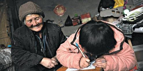 李显梅陪孙女写作业。孙女很懂事,是老人最大的骄傲。