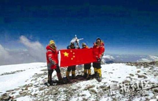 """资料图:鲁晓华在登顶时总会拿出一面印有""""安徽人""""字样的旗帜"""