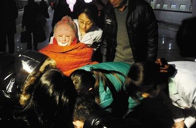周岩乘坐轮椅被护士推出站台。昨日,因拒绝求爱被烧成重伤的安徽女孩周岩,来京接受康复治疗。本报记者 尹亚飞 摄