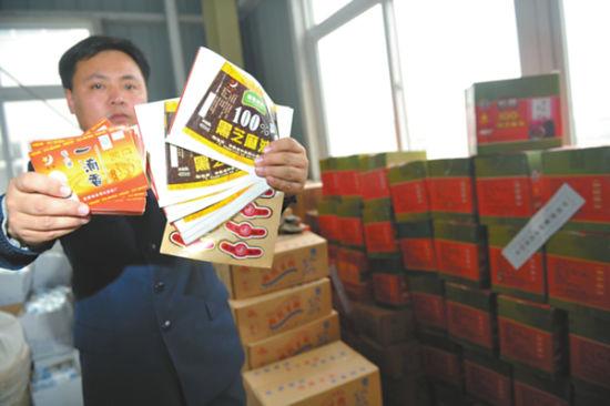 执法人员向记者展示黑作坊伪造的产品商标