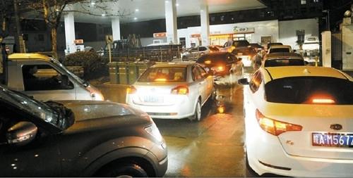 在合肥望江路一加油站,众多车主冒雨排队加油,两辆轿车还发生碰撞,一度堵住入口。