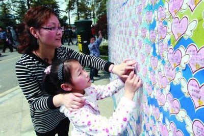 一个小女孩写下对外婆的思念,贴在思念墙上