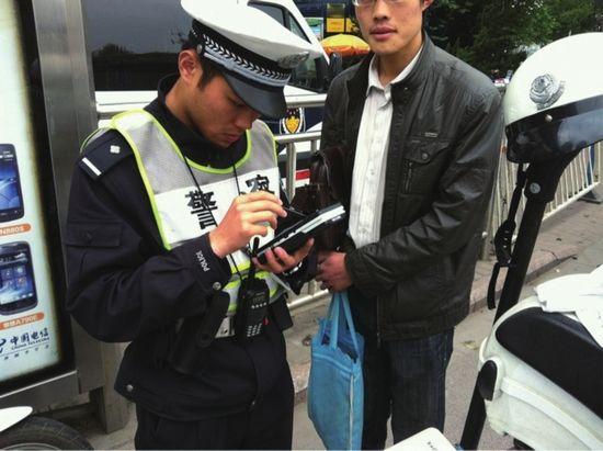 路面交警正在使用警务通执法。(图片由交警部门提供)