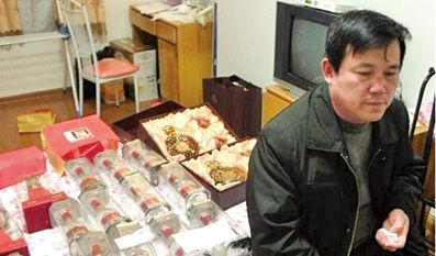 张斌闯入李辉在蚌埠某公寓后所拍摄的照片,李辉身后是15瓶五粮液和2瓶洋酒。