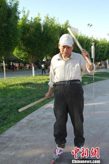 """73岁的张同义老汉正在边滑轮滑边练""""铁头功""""。"""