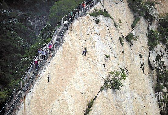 2012年5月10日,金锁关,一名环卫工人正向悬崖下移动。