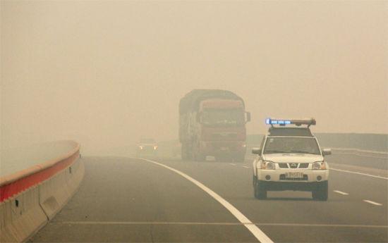 京台高速合徐北段能见度极低,沿蚌埠市路段高速公路管理部门启动应急预案,由警车开道。记者李勇/摄