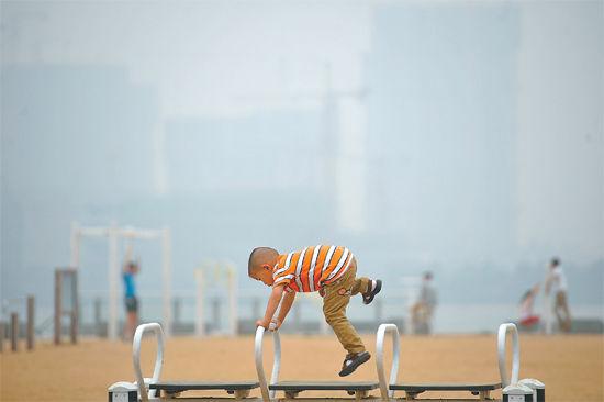 今天仍是雾霾天,儿童和老人应减少户外活动。记者陈群/摄