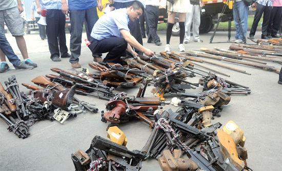 工作人员正在把收缴的枪支集中,准备回炉销毁。
