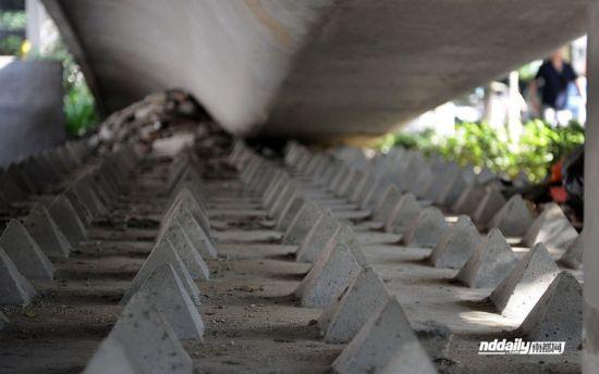 7月1日晚,在机场高速黄石入口高架桥底,百余平方米的平整水泥地,已被三角水泥尖覆盖。南都网/黎湛均