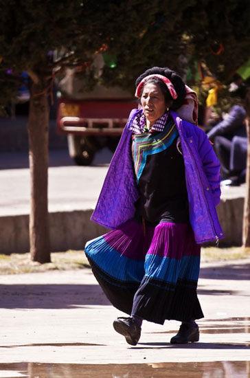 彝族的女人走起路来大步流星非常干练。