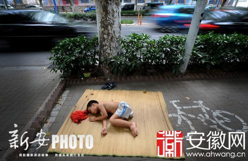 """芜湖路上,一个瓜农的孩子打着赤膊""""席地而卧"""",在树荫下午睡。"""