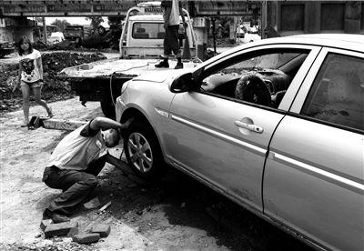 昨天,清障工作人员在青龙湖镇北车营村检查清理受损车辆。新华社发