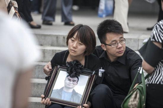 2012年7月25日,在北京广渠门桥下遇难的驾车人丁志健的追悼会在八宝山举行,亲友同事赶来为他送行。图为丁的妻子怀捧遗像,神情绝望。图/李昊