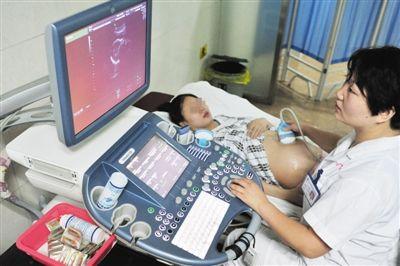 医生正为一名孕妇作B超检查