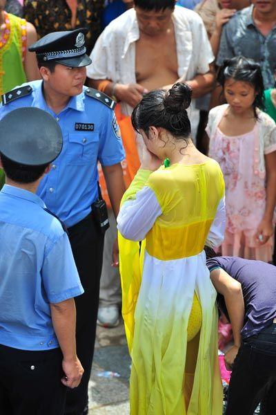 8月23日,海南省保亭黎族苗族自治县,嬉水节多名女子遭脱衣袭胸等性侵,警察保护现场遭侵犯的女子离开现场。