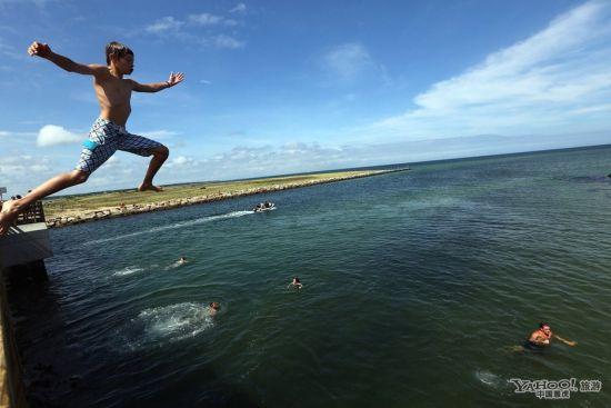 """一名儿童从""""大白鲨桥""""上跳入海水中"""