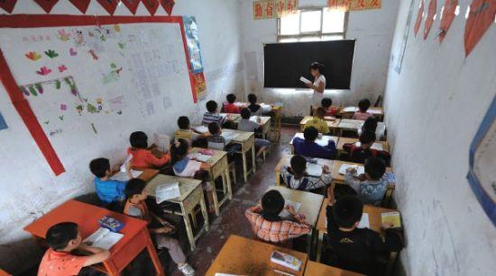 昨天,孩子们在合肥市嘉诚民工子弟学校的简陋教室内认真听讲。