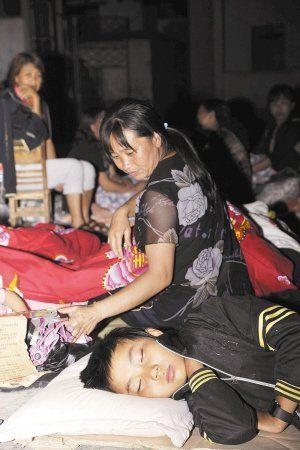 一名学生在母亲的陪伴下,在发达小学的操场安然入睡。