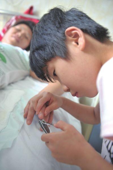琪琪在病房为母亲修剪指甲。(记者陈群/摄)