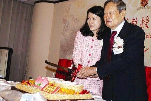 图为:杨振宁教授高兴地与妻子翁帆一起切生日蛋糕。