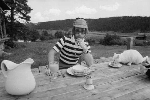 1974年在科罗拉多州的北美驯鹿牧场,埃尔顿·约翰与他的猫在户外用餐。