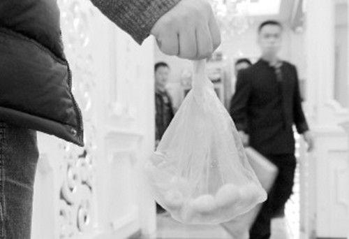 2月16日,在宁夏银川一火锅店内,一顾客将没吃完的涮品打包带走。