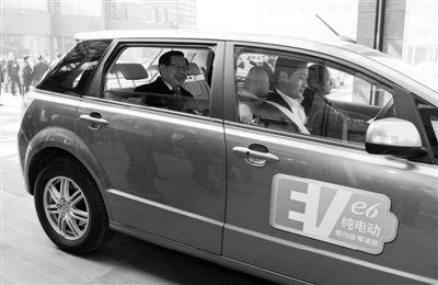 为了倡导环保,万钢特意乘坐纯电动车出行。新华社/发