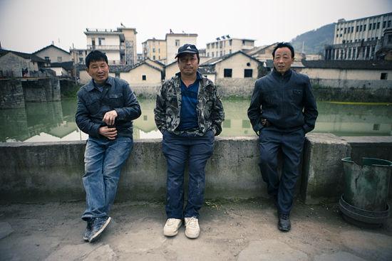 三位瓦匠师傅靠在堤坝上休息