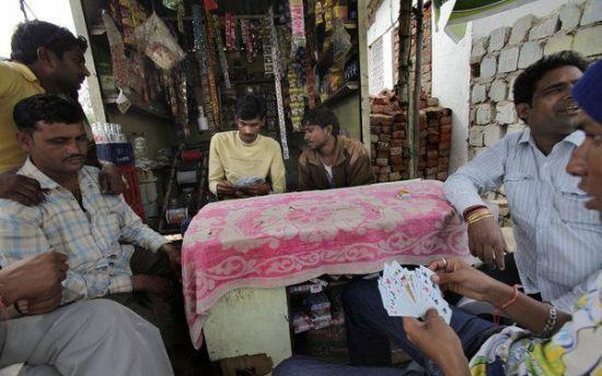 """男人们在村头打牌,他们中的许多人大都以拉皮条为生,为自家的姊妹介绍""""客人""""。"""