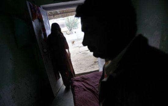 拉贾斯坦邦的一个红灯区,自Ingonia村的Preeti站在房间门口,坐在床上的是她的客人。