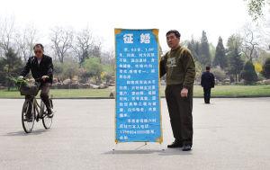 64岁的傅文老人每天早上6点多钟在劳动公园西门举牌征婚-记者石立飞摄