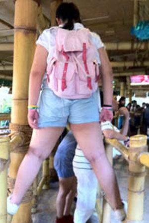 一女孩站在栏杆上排队等候