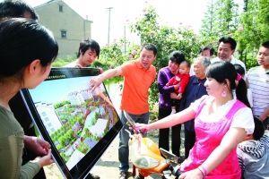 李全兴(图中穿橙色T恤男子)向村民讲解山泉新村小区规划图 资料图片