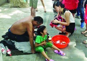 记者找到小女孩时,男子正带着她在中央路上乞讨