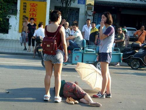 图为 两名女青年为受伤倒地的老人撑伞遮阳。