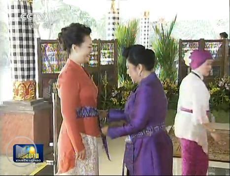 """印尼总统夫人阿妮亲手为彭丽媛系上印尼传统服饰""""纱笼""""。"""