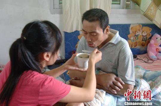 王琳芳的父亲患有痛风和结石,近年来病情加重,手脚肿大且皮肤发黑,疼痛时只能由女儿喂养。 陈龙山 摄