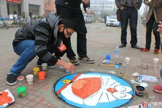 12月8日,20多名安师大美术爱好者协会的成员携带丙烯颜料和画笔来到花津校区第一、第二食堂外,开始在附近的窨井盖上作画。
