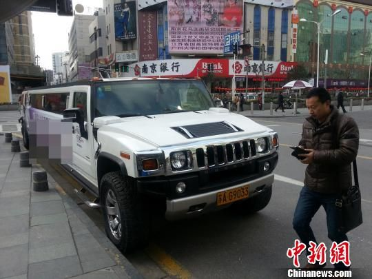 在南京新街口中央商场与悦荟广场之间的步行街上,一辆9.9米长的加长悍马汽车违停了好几天也不见车主开走,该车车身上印有广告。 卢辉 摄