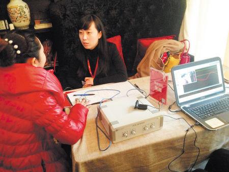 手指接上传感器后,女嘉宾(红衣者)的面部表情和心跳、脉搏等反应都在测谎仪的图谱仪上显示出来。 李卓 摄