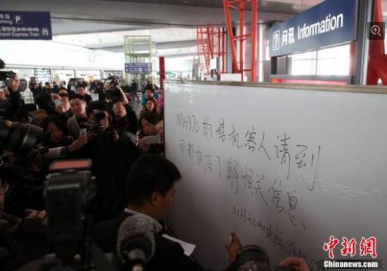 """当地时间3月8日,马来西亚航空公司一架载有239人的航班,在离开马来西亚首都吉隆坡后,与空中管制中心失去联系,据悉这架飞机的目的地是北京。航空公司在一份声明中表示,航班""""MH370""""是在当地时间凌晨2点40分与管制中心失去联系的,本应于北京时间6:30抵达北京。图为机场工作人员提示接机市民去丽都饭店等待。韩海丹 摄"""