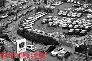 长安4S店对面的停车库已被刚到的新车停满。
