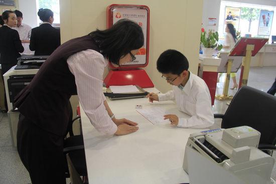 招行工作人员指导孩子办理业务