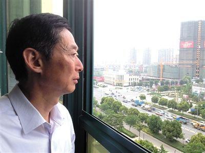 """5月21日,蚌埠市民政局内,于英生眼望窗外的高楼大厦。获释9个多月,他还在试着融入一座全新的城市。记者拍完照,他看着照片里的自己,""""唉,真的老了。""""新京报记者 贾鹏 摄"""