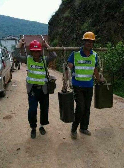 中国电信一线抢险队员客服重重困难,通过肩扛、背拖将油机发电用油徒步搬运到重灾区,为持续保障通信畅通奠定基础。