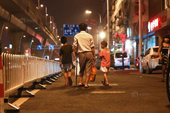夜晚,父子三人乞讨的背影