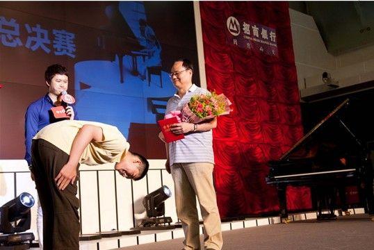"""""""金葵花""""钢琴赛上选手对父母鞠躬表示感恩。"""